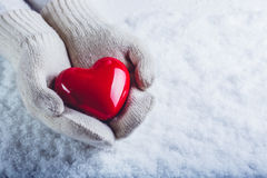 Las manos femeninas en blanco hicieron punto las manoplas con un corazón rojo brillante en un fondo de la nieve Amor y concepto d Imagenes de archivo