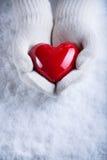 Las manos femeninas en blanco hicieron punto las manoplas con un corazón rojo brillante en un fondo del invierno de la nieve Amor Imagenes de archivo