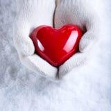 Las manos femeninas en blanco hicieron punto las manoplas con un corazón rojo brillante en un fondo del invierno de la nieve Amor Imagen de archivo libre de regalías