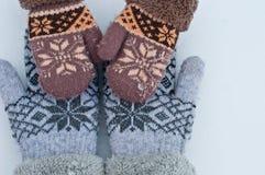 Las manos femeninas en manoplas están llevando a cabo las manos del bebé en manoplas contra la perspectiva de la nieve blanca Foto de archivo