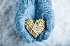 Las manos femeninas en trullo hicieron punto las manoplas con un corazón romántico entrelazado del vintage en un fondo de la niev Foto de archivo