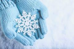 Las manos femeninas en trullo ligero hicieron punto las manoplas con el copo de nieve maravilloso chispeante en fondo de la nieve imagenes de archivo