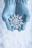 Las manos femeninas en trullo ligero hicieron punto las manoplas con el copo de nieve maravilloso chispeante en fondo de la nieve foto de archivo libre de regalías