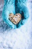 Las manos femeninas en trullo ligero hicieron punto las manoplas con el corazón de lino beige entrelazado en un fondo blanco de l fotos de archivo libres de regalías