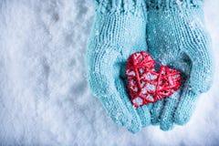 Las manos femeninas en trullo ligero hicieron punto las manoplas con el corazón rojo entrelazado en un fondo blanco de la nieve A Imagen de archivo libre de regalías