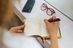 Las manos femeninas escriben con una pluma, cerca son concepto del negocio de los vidrios foto de archivo