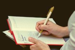 Las manos femeninas escriben en el diario aislado Fotos de archivo