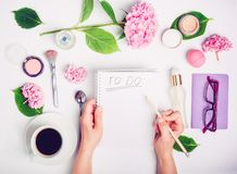 Las manos femeninas escriben para hacer la lista en el lugar de trabajo blanco con los accesorios femeninos, la taza de café, el  Imagen de archivo libre de regalías