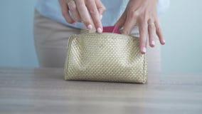 Las manos femeninas están buscando algo en el bolso cosmético almacen de metraje de vídeo