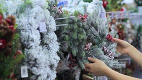 Las manos femeninas están considerando una guirnalda hecha a mano de la Navidad del trabajo almacen de metraje de vídeo