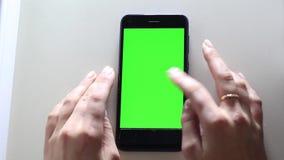 Las manos femeninas están llevando a cabo un dispositivo móvil con una pantalla verde Llave de Chrome almacen de video