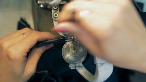 Las manos femeninas están pasando la tela forrada de piel a través de la máquina de coser almacen de video