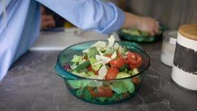 Las manos femeninas están poniendo las hojas cortadas de la lechuga en un cuenco de ensalada con los tomates y los pepinos en una almacen de metraje de vídeo