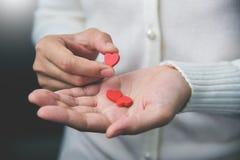 Las manos femeninas están sosteniendo píldoras Fotos de archivo