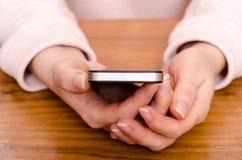Las manos femeninas están sosteniendo un teléfono elegante Imagenes de archivo