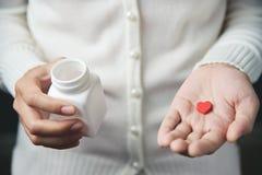 Las manos femeninas están sosteniendo una botella de píldora blanca y una píldora roja adentro él Imagen de archivo