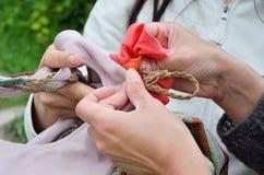 Las manos femeninas fijan encima de un adorno en el bolso Imagen de archivo
