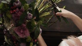 Las manos femeninas hermosas cortaron los troncos de flores con un pruner en una superficie oscura Estudio floral Tiro superior almacen de metraje de vídeo