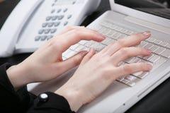 Las manos femeninas imprimen el texto en el teclado Fotografía de archivo