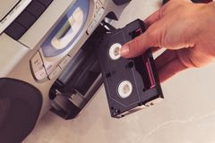 Las manos femeninas insertan el casete en centro de música fotos de archivo libres de regalías