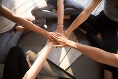 Las manos femeninas jovenes apiladas ven desde arriba imagenes de archivo