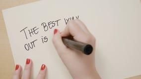 Las manos femeninas jovenes que escriben la mejor salida están siempre con cita de motivación del signo de exclamación en el Libr almacen de video