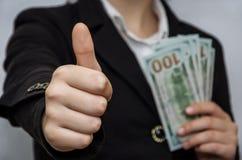 Las manos femeninas llevan a cabo dólares en el fondo blanco La mano muestra la 'clase ' imagenes de archivo