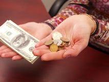 Las manos femeninas pesan monedas y denominaciones. Foto de archivo libre de regalías