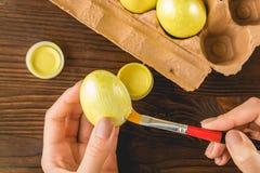 Las manos femeninas pintaron los huevos de Pascua en un color amarillo con un cepillo, Fotos de archivo