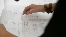 Las manos femeninas presentan bosquejos de la ropa almacen de video