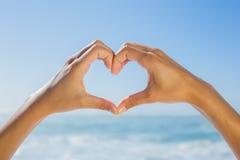 Las manos femeninas que hacen el corazón forman por el mar imágenes de archivo libres de regalías