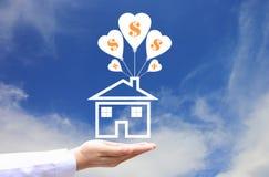 Las manos femeninas que llevan a cabo el símbolo de la casa con el globo y el símbolo del dólar en fondo del cielo azul, ahorran  imagen de archivo libre de regalías