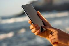 Las manos femeninas que sostienen el nuevo iPhone 6s espacian gris Imágenes de archivo libres de regalías