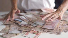 Las manos femeninas recogen mucho dinero en una tabla blanca, billetes de banco tailandeses, billetes de banco rusos almacen de video