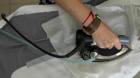 Las manos femeninas se cosen con un paño del gris del hierro del ` s del sastre