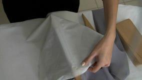 Las manos femeninas se cosen con un paño gris del hierro del ` s del sastre para el trabajo adicional con ella almacen de video