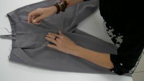 Las manos femeninas se cosen con una aguja almacen de video