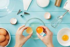 Las manos femeninas separan la clara de huevo de la yema de huevo para la crema azotada Fotos de archivo libres de regalías