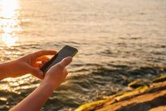 Las manos femeninas sostienen el teléfono Utilice el teléfono para conectar en viaje concepto del recorrido Vista del mar y de la Fotos de archivo