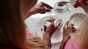 Las manos femeninas sostienen los huevos revueltos en una cacerola, intentando separar la comida de platos almacen de video