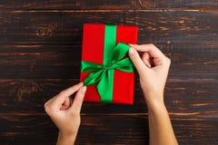 Las manos femeninas sostienen un regalo rojo con una cinta verde En el fondo de una tabla de madera, visión superior fotografía de archivo libre de regalías