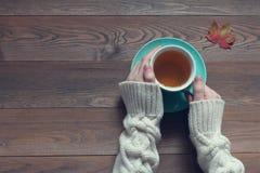 Las manos femeninas sostienen una taza con té verde en una tabla de madera Foto de archivo