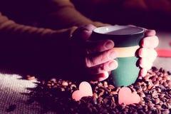 Las manos femeninas sostienen una taza de café con las habas Foto de archivo