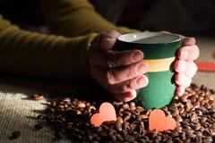 Las manos femeninas sostienen una taza de café con las habas Foto de archivo libre de regalías