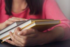 Las manos femeninas sostienen varios nuevos libros imagenes de archivo
