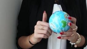 Las manos femeninas sostienen y giran el globo de la bola del juguete de la tierra