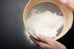 Las manos femeninas tamizan la harina en un fondo negro, visión superior fotografía de archivo