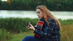 Las manos femeninas tocan la guitarra Una chica joven despreocupada feliz toca la guitarra mientras que ella está en el bosque to metrajes