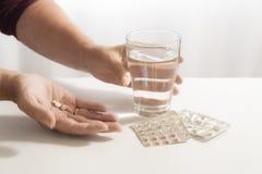 Las manos femeninas toman píldoras y un vidrio del agua, paquete de ampolla en el th imagenes de archivo