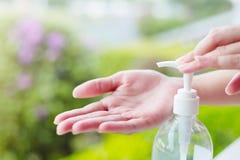 Las manos femeninas usando lavado dan el dispensador de la bomba del gel del desinfectante Fotografía de archivo libre de regalías